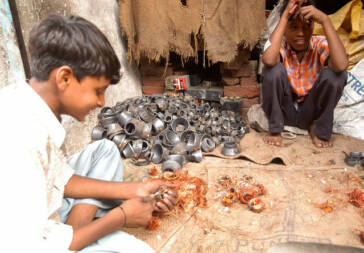 Children extract copper from discarded computer parts. New Delhi