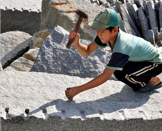 Kind bearbeitet GrabsteinKind in Vietnam arbeitet in einem Steinbruch |  Bild: ©  ILO in Asia and the Pacific [CC BY-NC-ND 2.0]  - flickrKind bearbeitet Grabstein