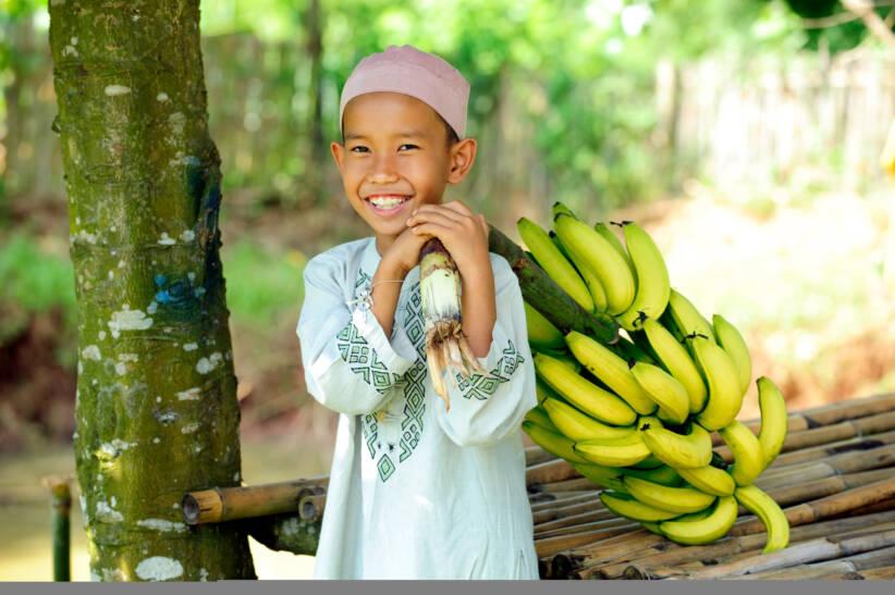 |  Bild: Happy Muslim boy holding bananas © Distinctiveimages | Dreamstime.com [Royalty Free]  - Dreamstime
