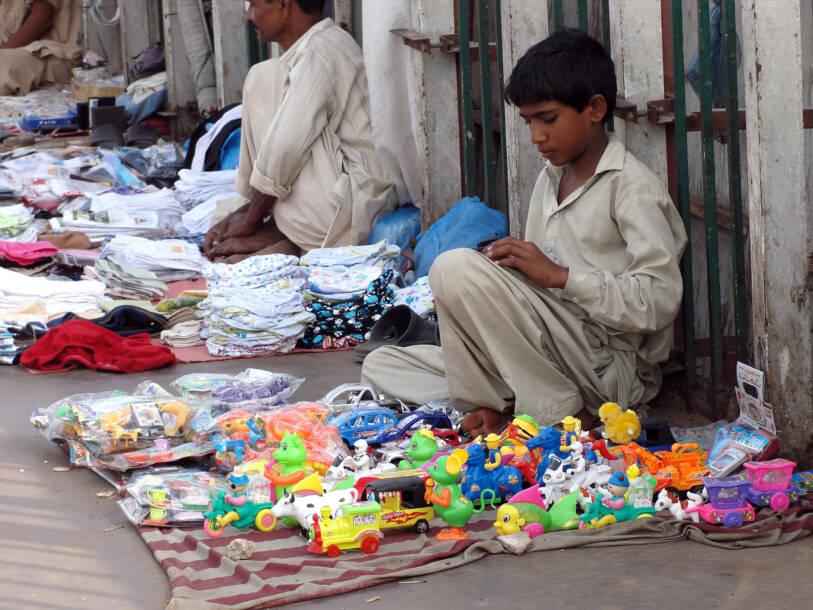 Ein Kind verkauft Spielzeug auf der StraßeEin Kind verkauft Spielzeug auf der Straße |  Bild: Lavori infantili © Owaisphotography [Royalty Free]  - DreamstimeEin Kind verkauft Spielzeug auf der Straße