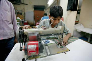 Ein Kinderarbeiter an der Nähmaschine