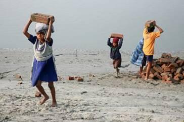 Kinderarbeiter:innen tragen Ziegelsteine
