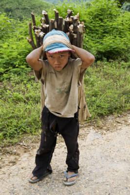 Ein Kinderarbeiter in Laos schleppt Holz