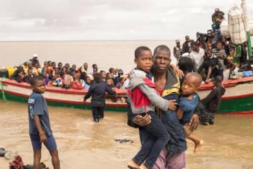 Ein Vater trägt seine zwei Söhne von einem großen Holzboot an Land.