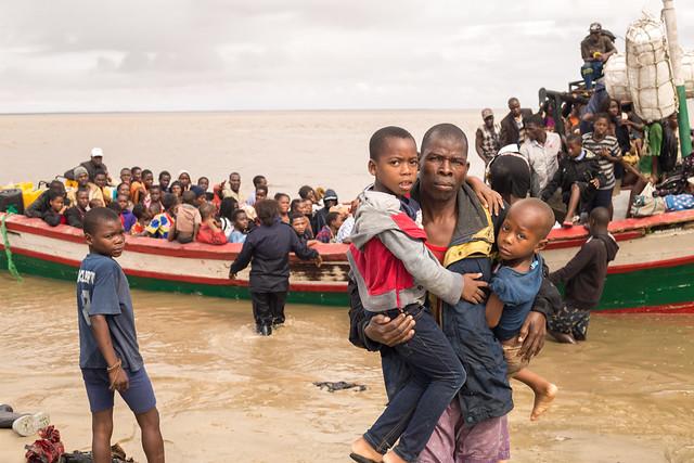 Ein Vater trägt seine zwei Söhne von einem großen Holzboot an Land.Evakuierung in Beira, Mosambik |  Bild: Climate Centre Cyclone Idai, Mozambique, evacuees in Beira, 21 March 2019 (Denis Onyodi: IFRC/DRK/Climate Centre) © Denis Onyodi: IFRC/DRK/Climate Centre [CC BY-NC 2.0]  - flickrEin Vater trägt seine zwei Söhne von einem großen Holzboot an Land.