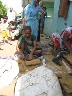 Ms Usha Ranjitsingh squats on the pavement outside her home, making incense sticks.